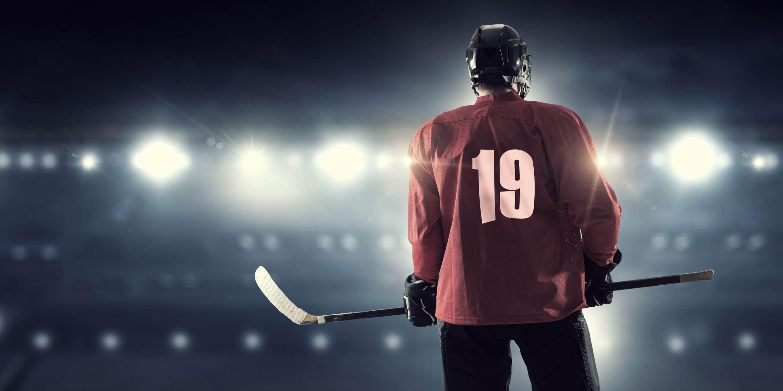 Hockey player in red uniform on ice rink in spotlight